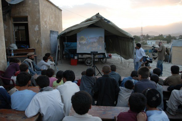 The agricultural bike can handle steep and rugged roads, allowing the film to be shown in hard-to-access areas. Here, children watch outside, with the screen protected from the sun