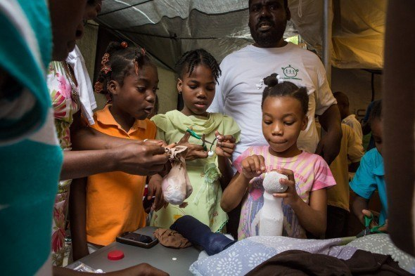 Making puppets in Haiti: Hands-on activities are extremely popular, and help children express feelings through puppet play, allowing facilitators or care workers to pick up on concerns