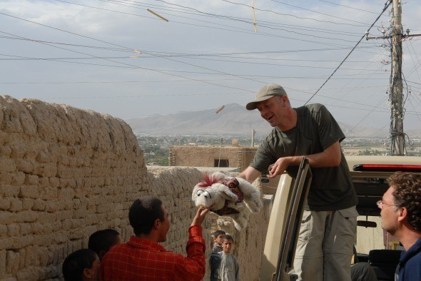 Patron Hugo Speer entertains children in Kabul, Afghanistan, with No Strings field puppet Hamish