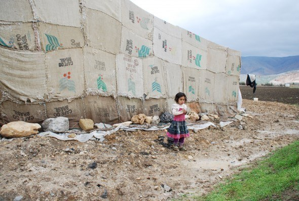 A little Syrian girl is dwarfed by surrounding makeshift tents in a camp near the border in Lebanon's Bekaa Valley