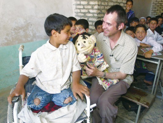 Patron Neil Morrissey with puppet Chuchi and a boy in Herat, Afghanistan, victim of horrific landmine injuries