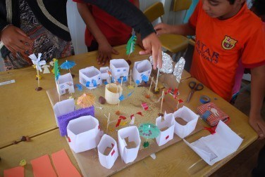 Children make a model of the Red Top, Blue Top village showing the tensions that exist before the Wise Man's intervention