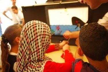 Iraq. IDP camp children, shadow puppet 'win win' scene, back