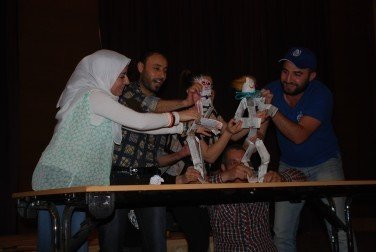 Participants make table top puppets from newspaper and practice making them dance