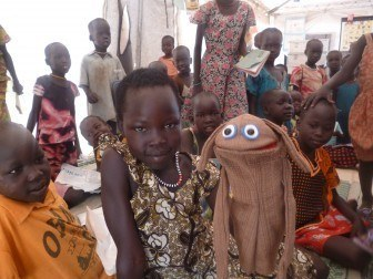 A little girl at Mingkaman IDP camp tries her hand puppeteering for the first time